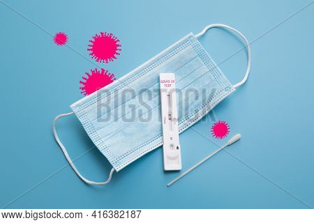 Rapid Coronavirus Test And A Medical Mask On The Blue Background With Pink Coronavirus Silhouettes.