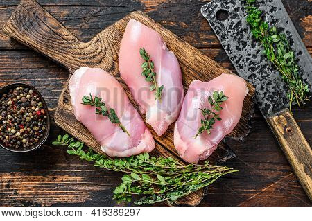Raw Chicken Skinless Thigh Fillet On A Wooden Cutting Board. Black Background. Top View