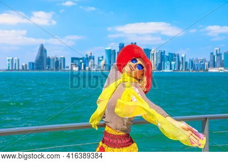 Carefree Caucasian Woman Enjoyis The Views Of Doha West Bay Skyline. Happy Tourist In Summer Holiday