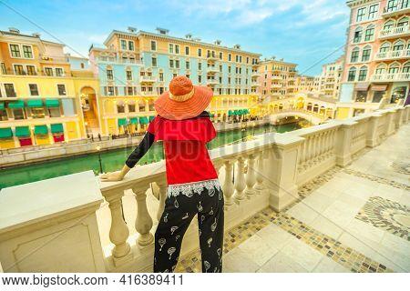 Woman Looking Famous Bridge In Venice Doha City. Caucasian Tourist At Qanat Quartier In The Pearl-qa