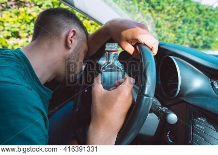 Drunk Man Sleeping On The Steering Wheel In His Car With A Bottle Of Vodka In His Hands. Drunk Drive
