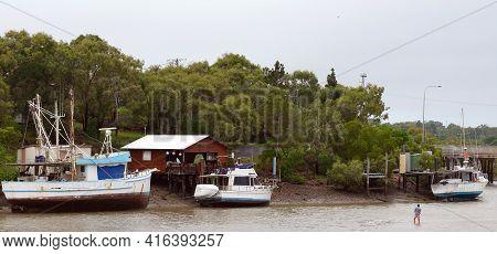 Yeppoon, Queensland, Australia - April 2021: Boats Moored Beside A Hut In A Coastal Creek At Low Tid
