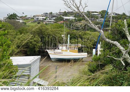 Yeppoon, Queensland, Australia - April 2021: A Wooden Boat Moored In A Mangrove Creek At Low Tide Se