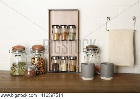 Set Of Spices And Different Dishware On Wooden Table Near White Brick Wall In Kitchen