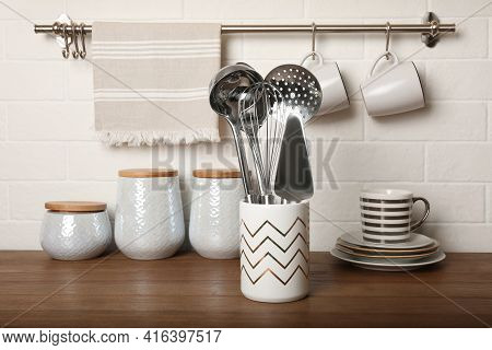 Steel Utensils And Different Dishware On Wooden Table Near White Brick Wall In Kitchen
