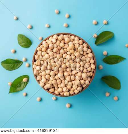 Wooden Bowl With Raw Dried Chickpeas On A Blue Background With Green Leaves. Concept Of A Balanced D