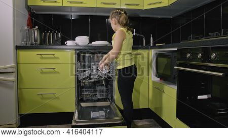 Smart Girl Learning To Use Dishwasher. Stylish Modern Built In Kitchen Appliances In Green Black. Ch