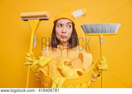 Serious Thoughtful Female Maid Holds Mop And Broom In Both Hands Busy Doing Household Chores Poses N