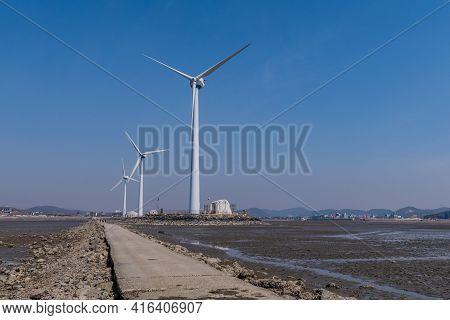 Pyeongtaek; South Korea: March 31, 2021:three Wind Turbines Beside Causeway In Tando Port At Low Tid