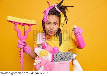 Cleaning And Housekeeping Concept. Serious Housekeeper With Dreadlocks Holds Chemical Detergent And