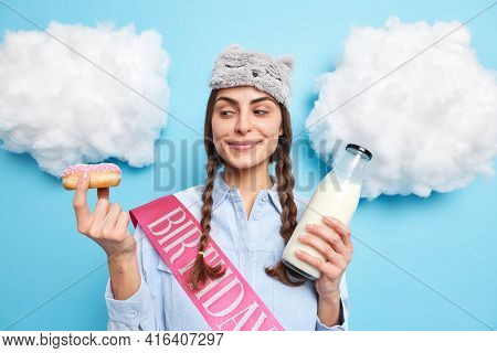 Pleased European Woman With Two Pigtails Looks At Tasty Glazed Doughnut Going To Eat It With Fresh M
