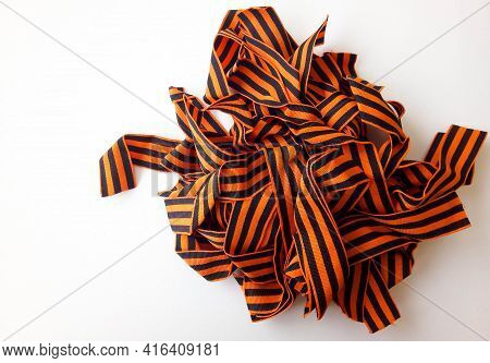 The St. George Ribbon-a Symbol Of Russian Military Valor-is Lying In A Pile On A White Background. S