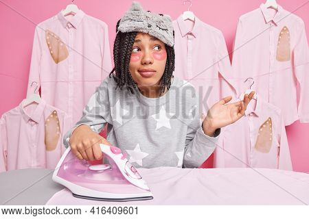 Hesitant Woman Shrugs Shoulders While Ironing Clothes Uses Electric Iron Dressed In Nightwear Applie