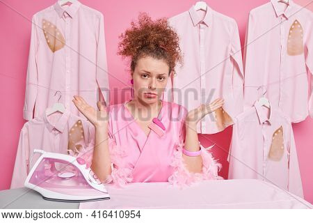 Clueless Curly Woman Spreads Palms Feels Hesitant Does Housework Wears Dressing Gown Irons Folded Cl