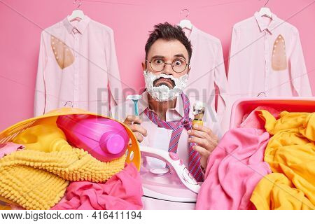 Surprised Puzzled Man Hurries For Work Shaves And Irons At Same Time Holds Razor And Shaving Brush S