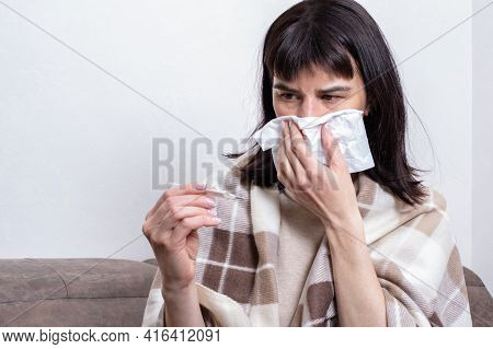 A Sick Woman Blows Her Nose Into A Paper Handkerchief, Blows Her Nose And Holds A Thermometer. A Cau