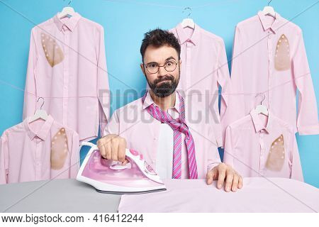 Photo Of Puzzled Tired Bearded Man Strokes Clothes On Ironing Board Gets Dresses For Formal Buisness