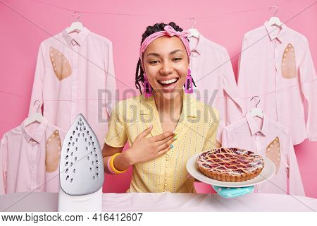 Happy Dark Skinned Young Woman Smiles Broadly Expresses Positive Emotions Shows Delicious Baked Pie
