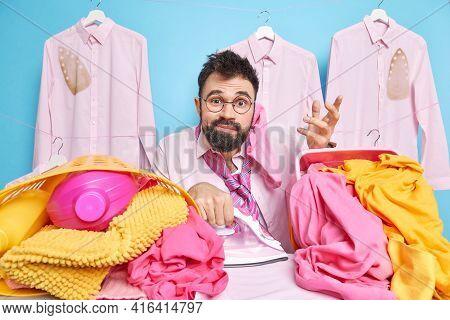 Clueless Hesitant Bearded Man Poses Against Laundry Baskets Has Sock On Ear Shrugs Shoulders Doesnt