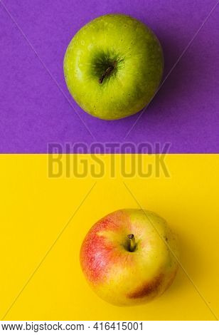 Green Apple And Yellow-red Apple, On A Half Purple And Half Yellow Background
