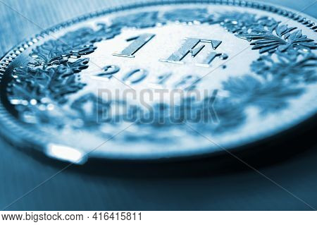 1 One Swiss Franc Coin Close-up. Dark Blue Tinted Illustration On An Economic, Business, Entrepreneu