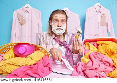 Multitasking Man With Long Red Hair Busy Doing Ironing Of Clothes And Shaving At Same Time Being In