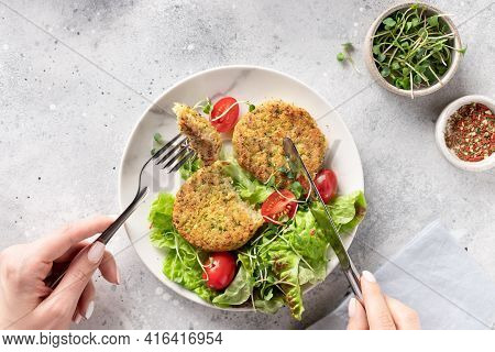 Woman Eating Vegan Broccoli And Quinoa Burgers