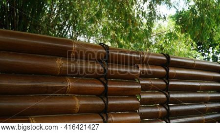 Dark Brown Bamboo Arrangement With Black Rope, Blurry Background Of Bamboo Leaves. Can Be A Design B