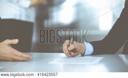 Business People Discussing A Contract At Meeting Or Negotiation, Sitting At The Desk Together, And A