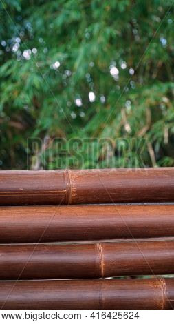 Four Bamboos In Dark Brown Color With Blurred Bamboo Leaf Background. Can Be A Design Background Mat