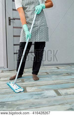 Bearded Man In Gloves With Mop In Hand Cleaning Floor In The House