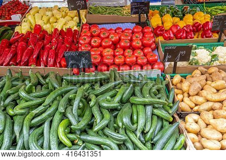 Cucumber, Tomatoes And Potatoes For Sale At A Market