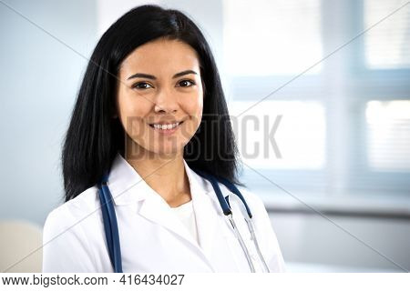 ?lose-up portrait of smiling young hispanic female doctor.
