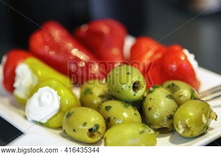 Freshly Garnished Green Olives And Red Pointed Peppers Stuffed With Cream Cheese