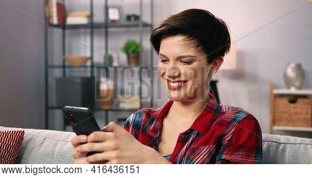 Smiling Girl Relaxing And Sitting On Sofa At Home While Using Cell Phone. Woman Texting And Chatting