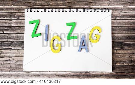 The Word Zigzag Consists Of Multi-colored Letters On A White Notebook That Lies On A Wooden Table