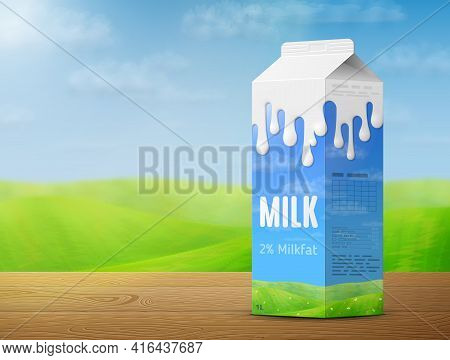 Milk Package On Wooden Table On Background Of Blurred Landscape. Cow Milk Gable Top Carton With Mead