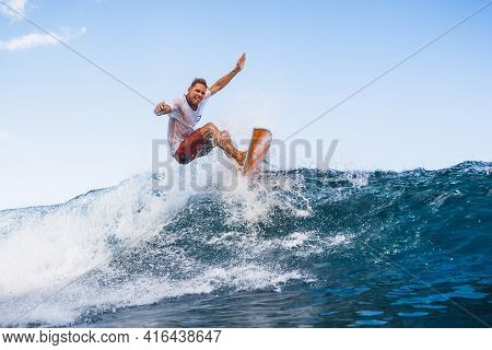 December 09, 2020. Bali, Indonesia. Surfer With Surfboard At Ocean Wave. Surfing In Ocean At Waves