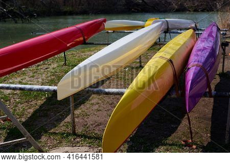 Colorful Canoes Lie On The River Bank. Close-up View From The Top Side