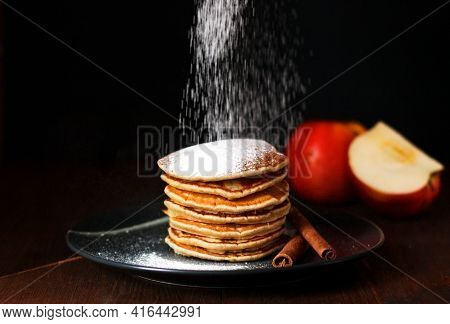 American Pancakes With Cinnamon And Apples. Healthy Breakfast On Dark Background, Sprinkled With Pow