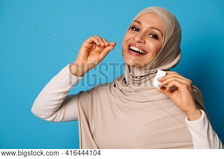 Cute Arab Woman With Covered Head And Perfect Smile Using A Dental Floss And Posing Over Blue Backgr