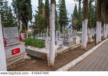 Birgi, Izmir, Turkey - 03.09.2021: Turkish Graveyard With Trees And Marble Ornaments And Turkish Fla