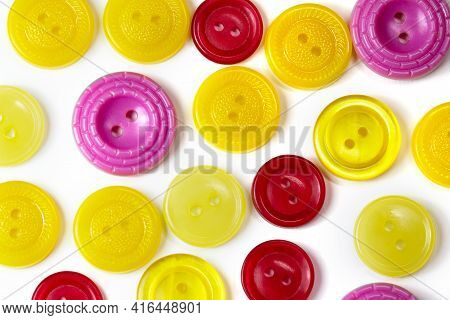 Colorful Yellow Red And Pink Buttons On A White Background. Old Vintage Buttons Close Up. Copy Space