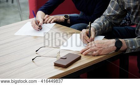 An Adult Woman And A Man, Sitting At A Table In The Office, Fill Out Documents Or Forms. The Concept