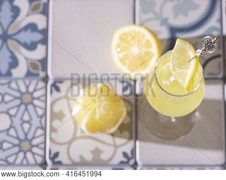 Limoncello, Traditional Italian Liquor On A Light Concrete Background In The Rays Of The Sun. Next T