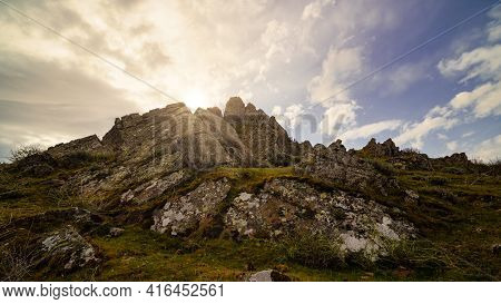 Golden Sunrise On The Mountain With Sun Rays Coming Out From Behind The Rocks And Idyllic Atmosphere