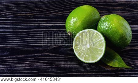 Fresh Green Limes And Half A Lime On The Dark Wooden Background Of The Kopi Space