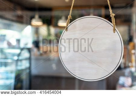 Blank Vintage Wooden Sign Board Hanging On Glass Door In Modern Cafe Restaurant, Copy Space For Text