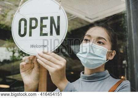 Open. Waitress Staff Wearing Protection Face Mask Turning Open Sign Board On Glass Door In Modern Ca