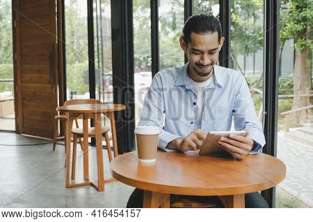 Businessman Using Digital Mobile Tablet With Hot Coffee Cup On Desk Sitting And Keep Distance To Pro